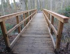 Die neue Brücke über dem Bach zum Wald
